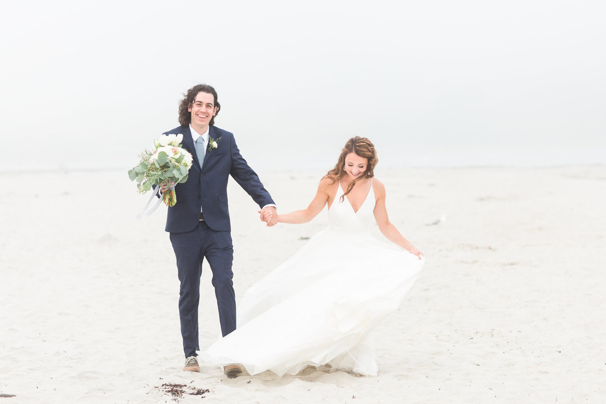 Bride and Groom holding hands walking along beach