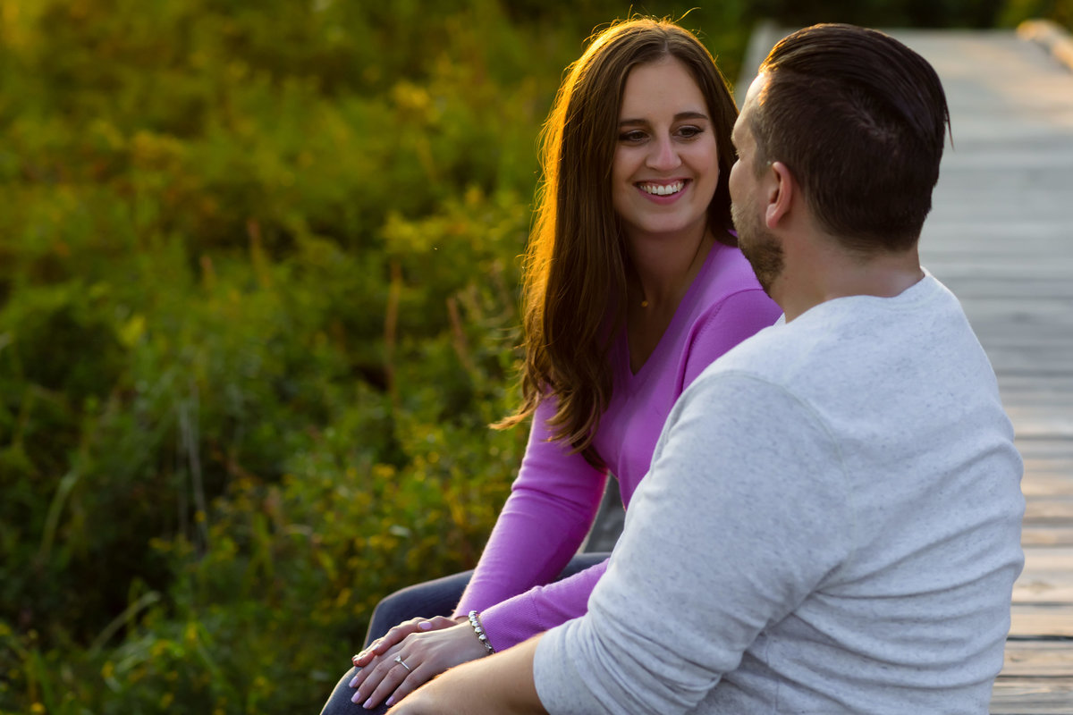The couple sits on the wooden walkways at Kettle Cove Maine engagement session