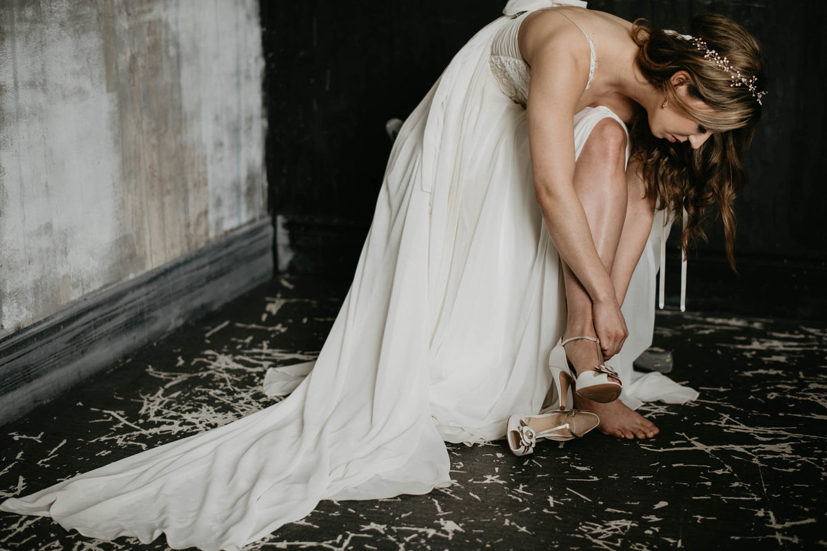 bride putting on her white wedding heels