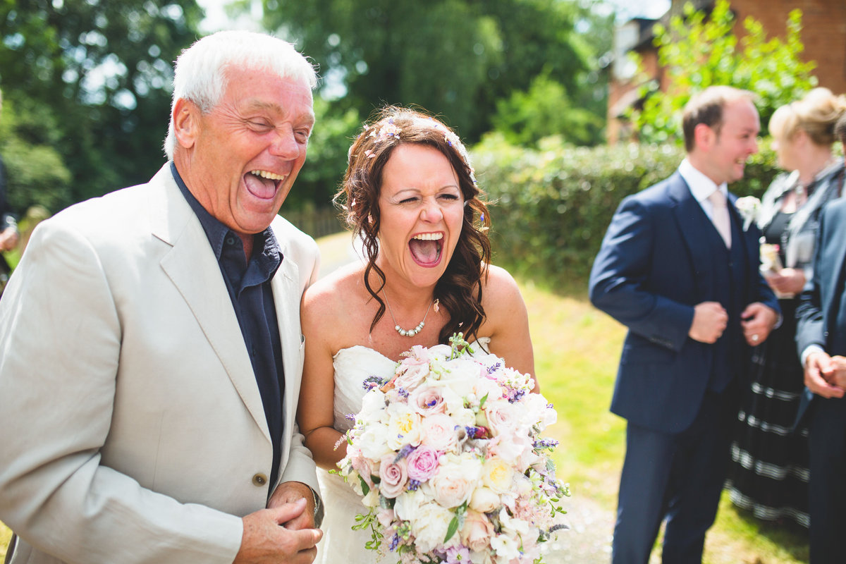 bride with friend and red floral bouquet laughing outside shropshire church