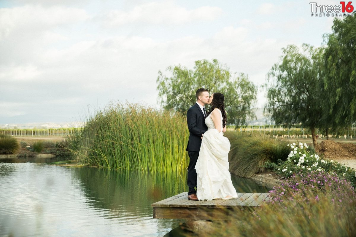 Bride and Groom share an intimate moment on a lake dock