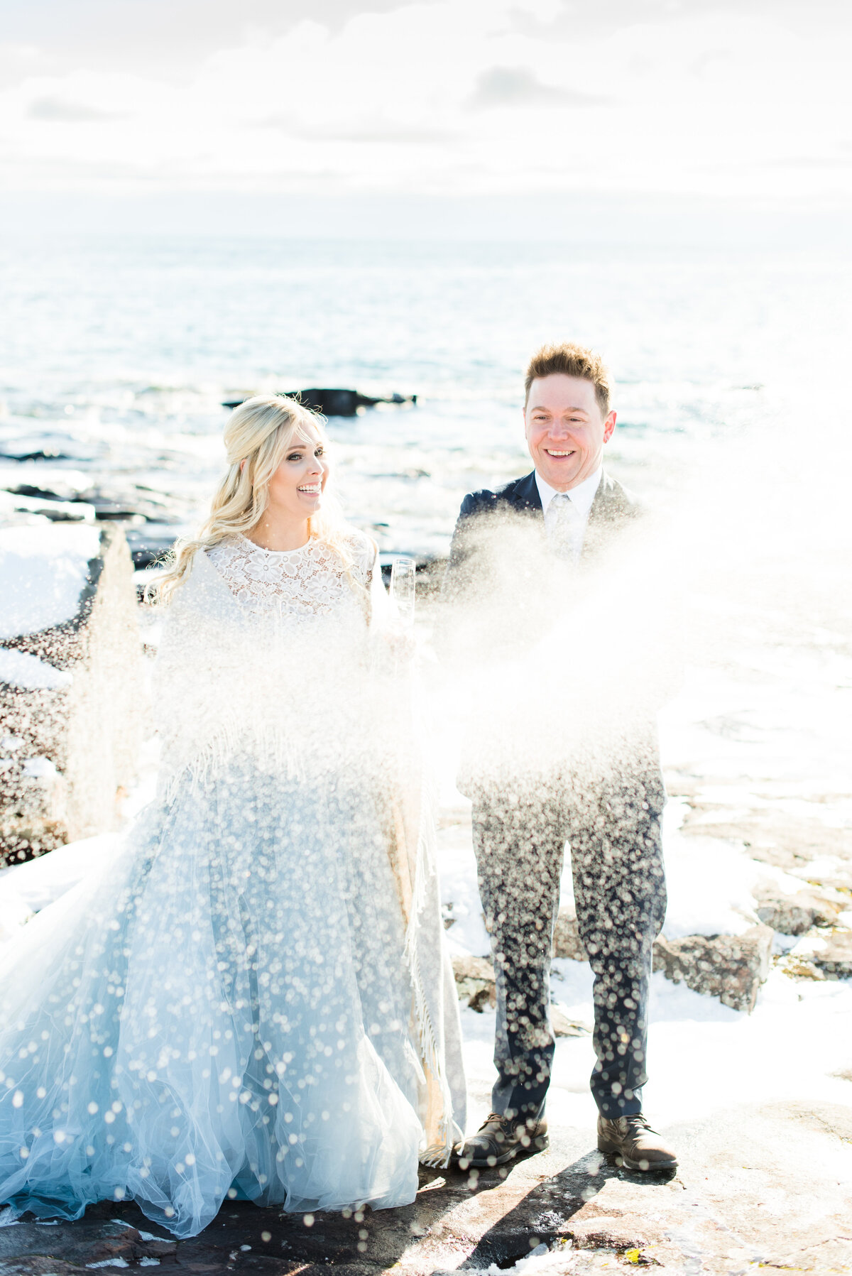 A bride and groom pop a bottle of champagne during their winter wedding in Thunder Bay