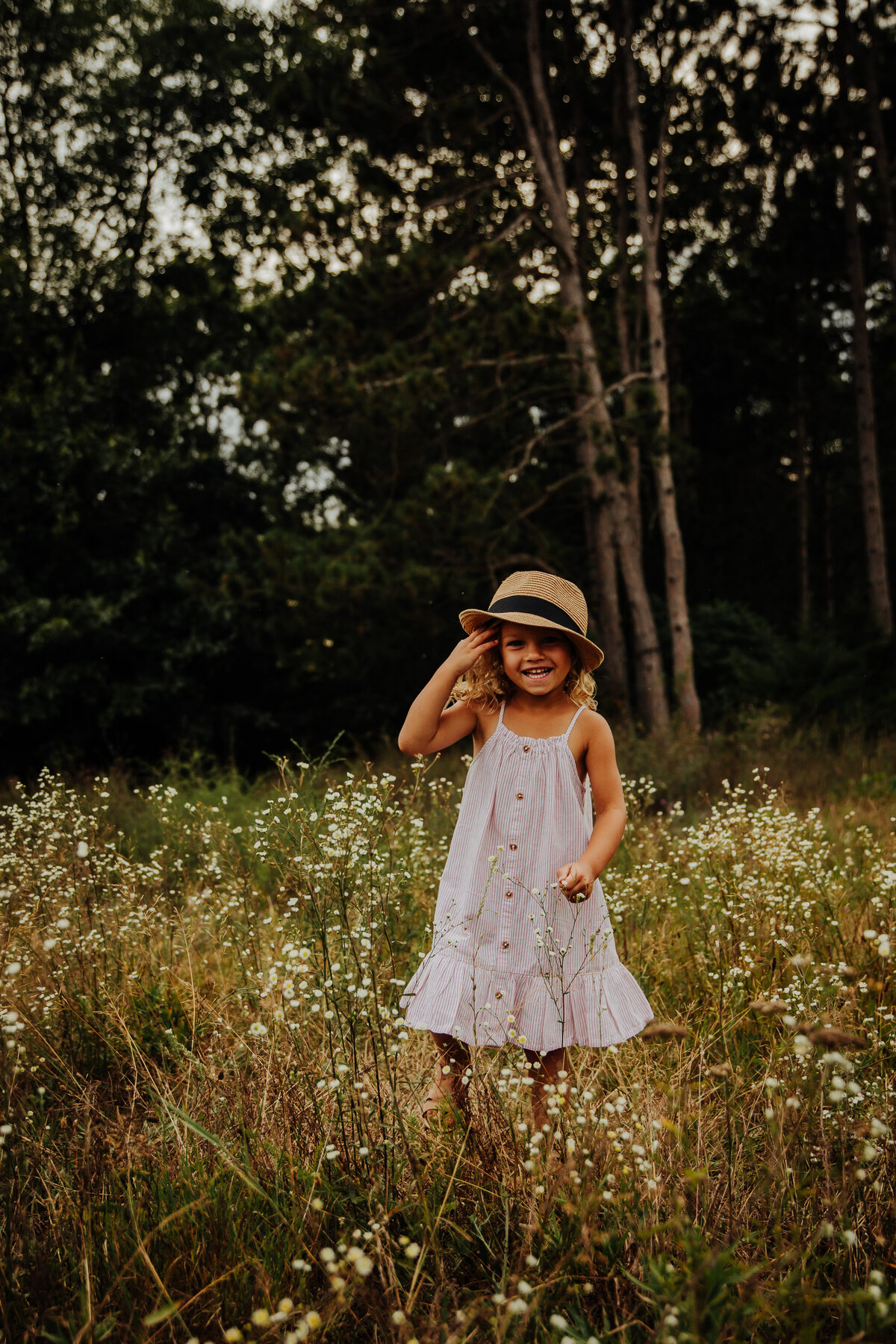 little girl in fedora hat in field of flowers