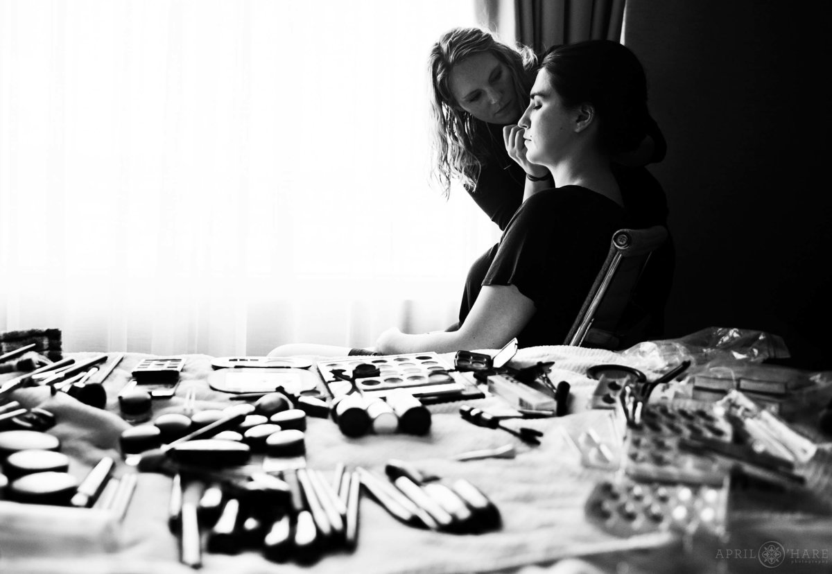 Make up scattered across hotel room bed as bride gets her make up done in a B&W photo in Boulder Colorado