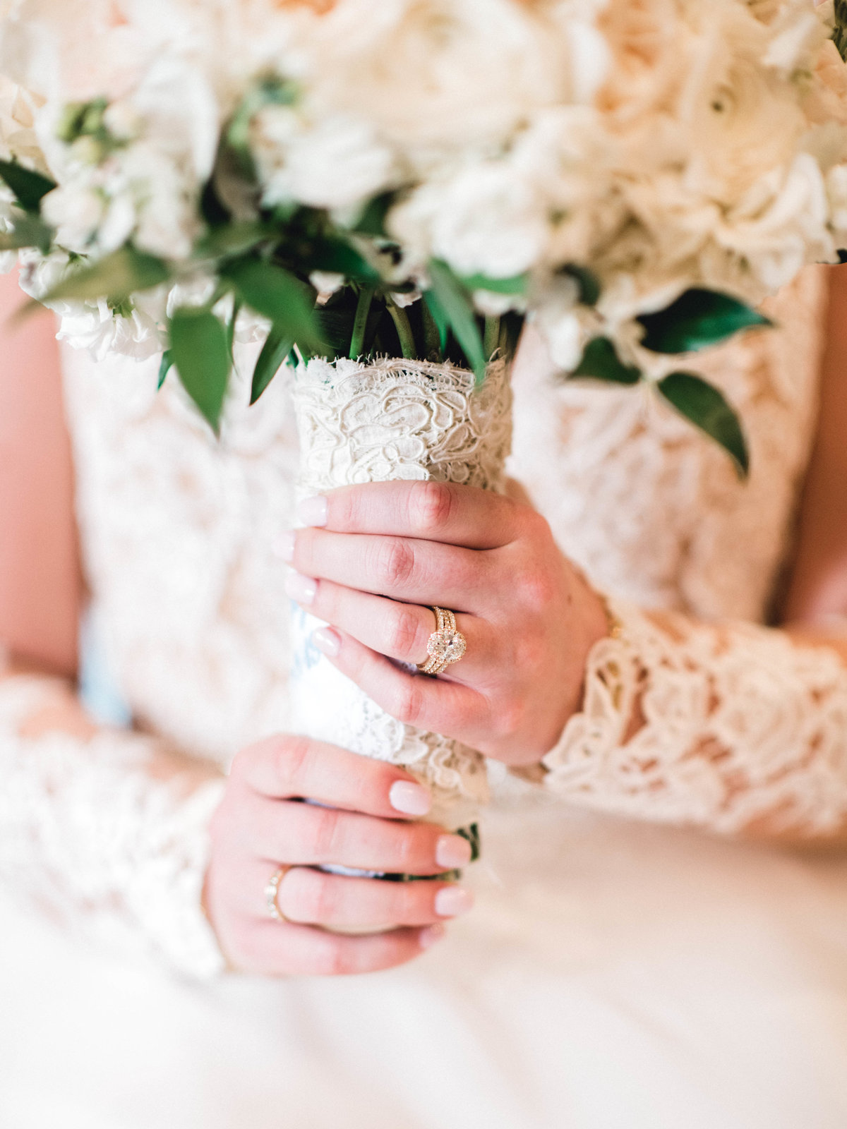 Bride holding bouquet wrapped in lace from mothers gown
