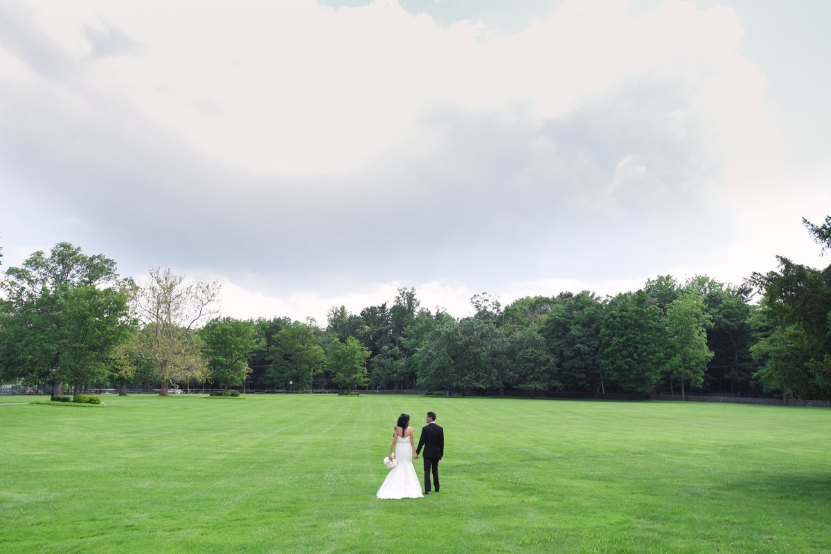 Bride and groom walking at the grounds of Glen Cove Mansion