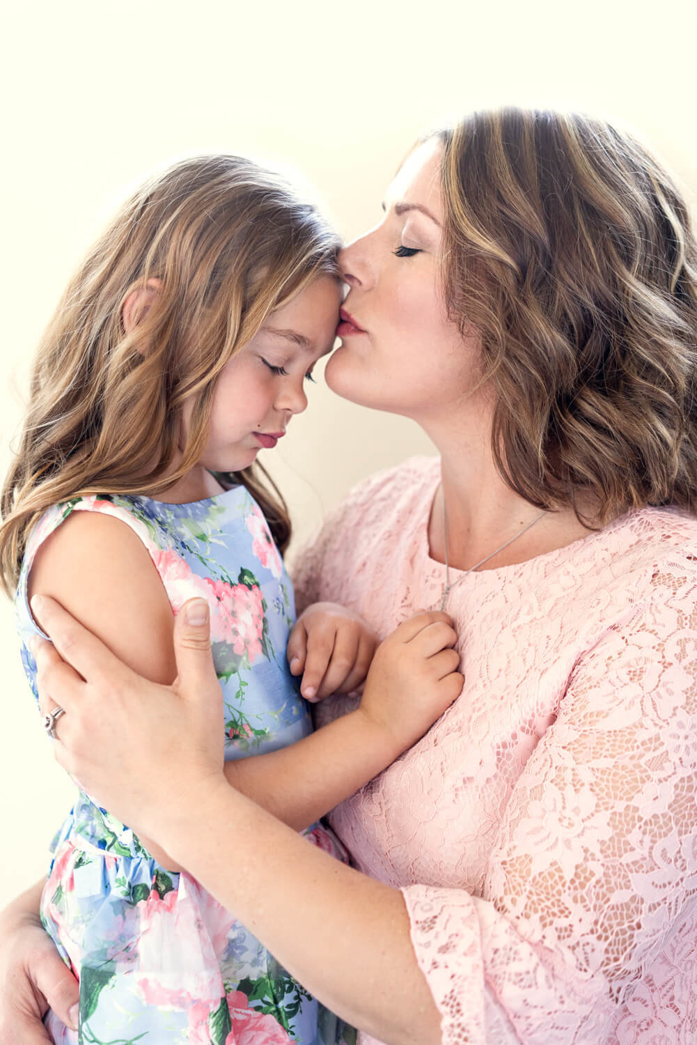 Mom giving daughter a kiss on the forehead in a portrait photoshoot in Davis California
