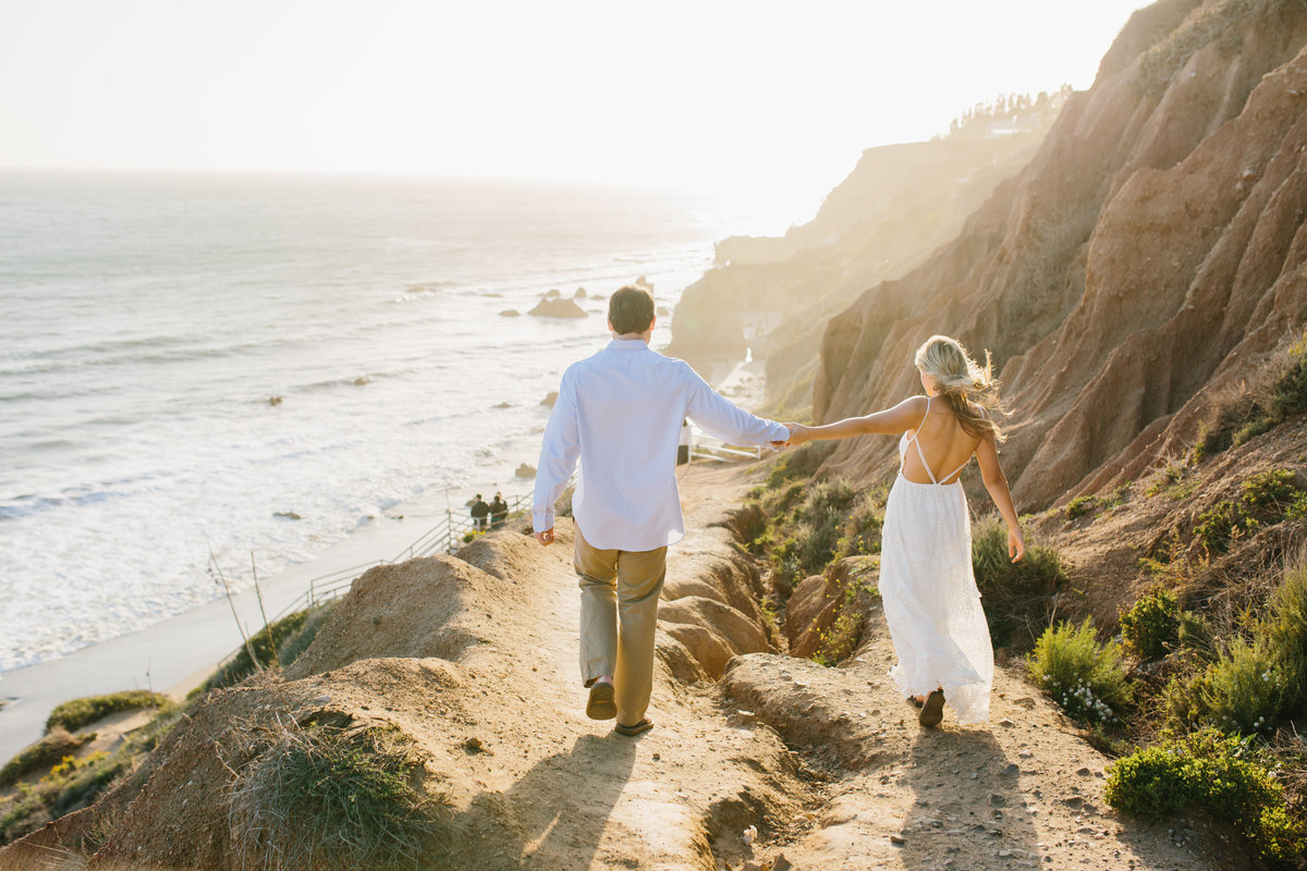 Couple walking down a path holding hands to the beach in Malibu California