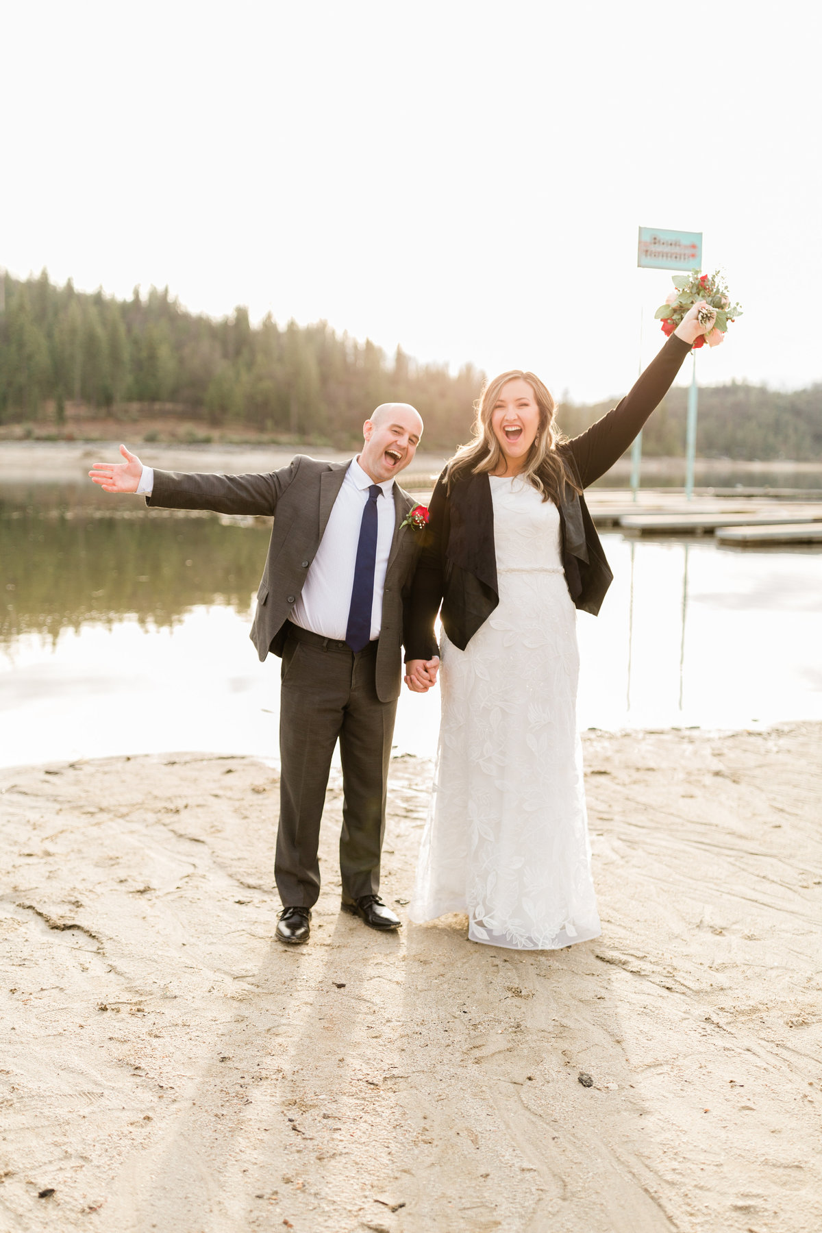 excited newlyweds cheering on the shores of bass lake