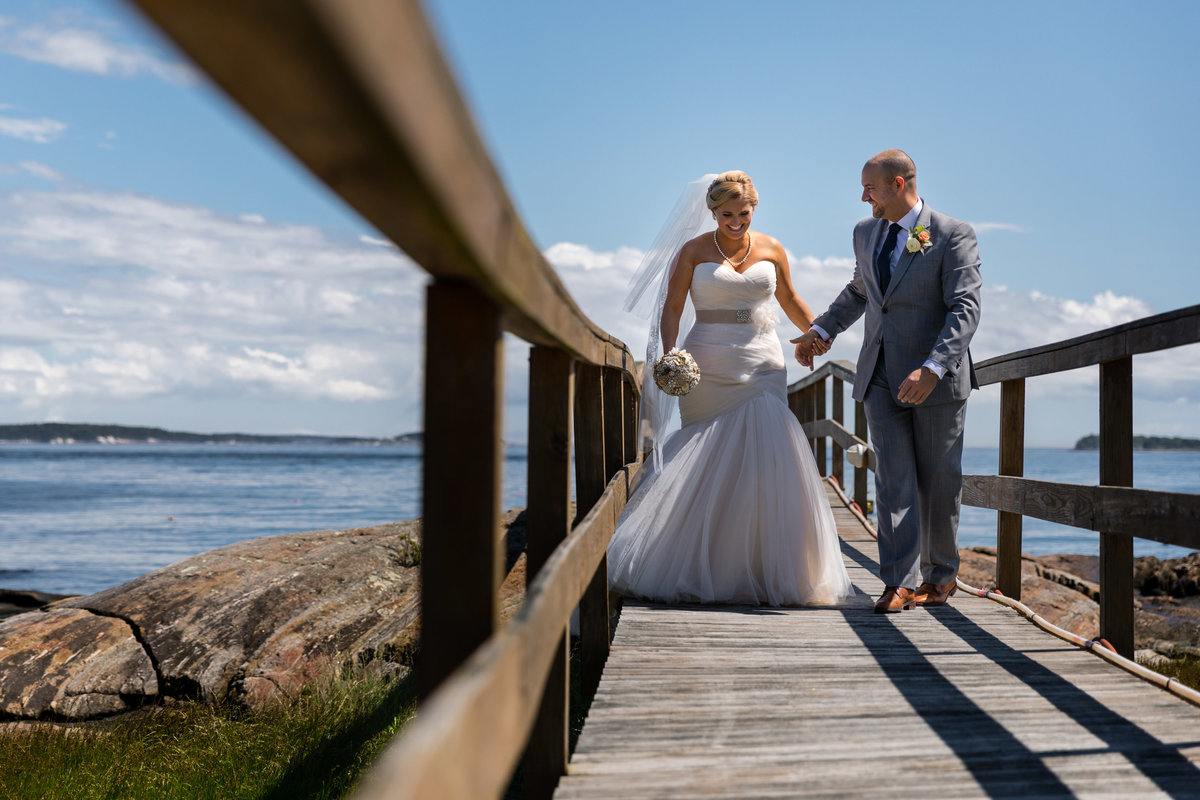 The bride and groom walk along the dock in Harpswell Maine