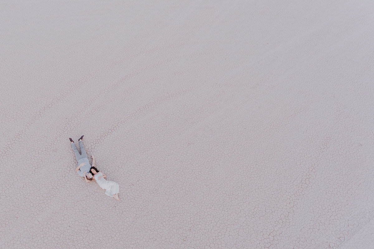 Lake Tahoe elopement photos bride and groom lay on desert playa together