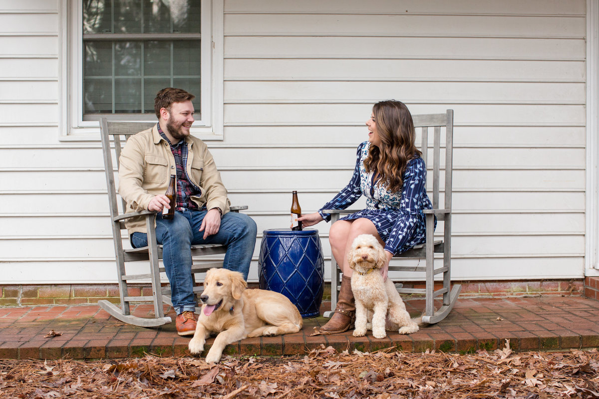 couple on a porch with dogs and beer during engagement session