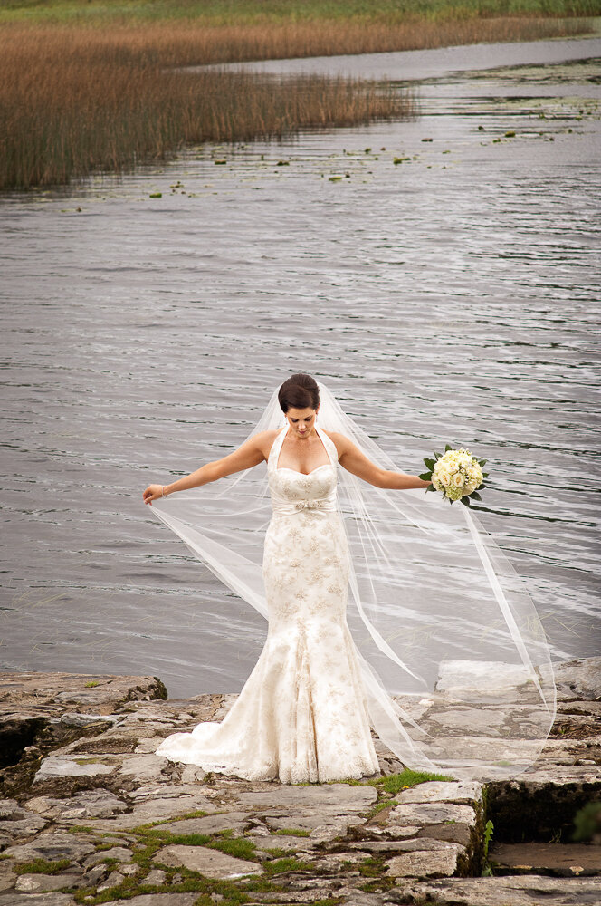 brunette bride wearing a lace, trumpet style, halter neck wedding dress and long veil standing at lake in Killarney