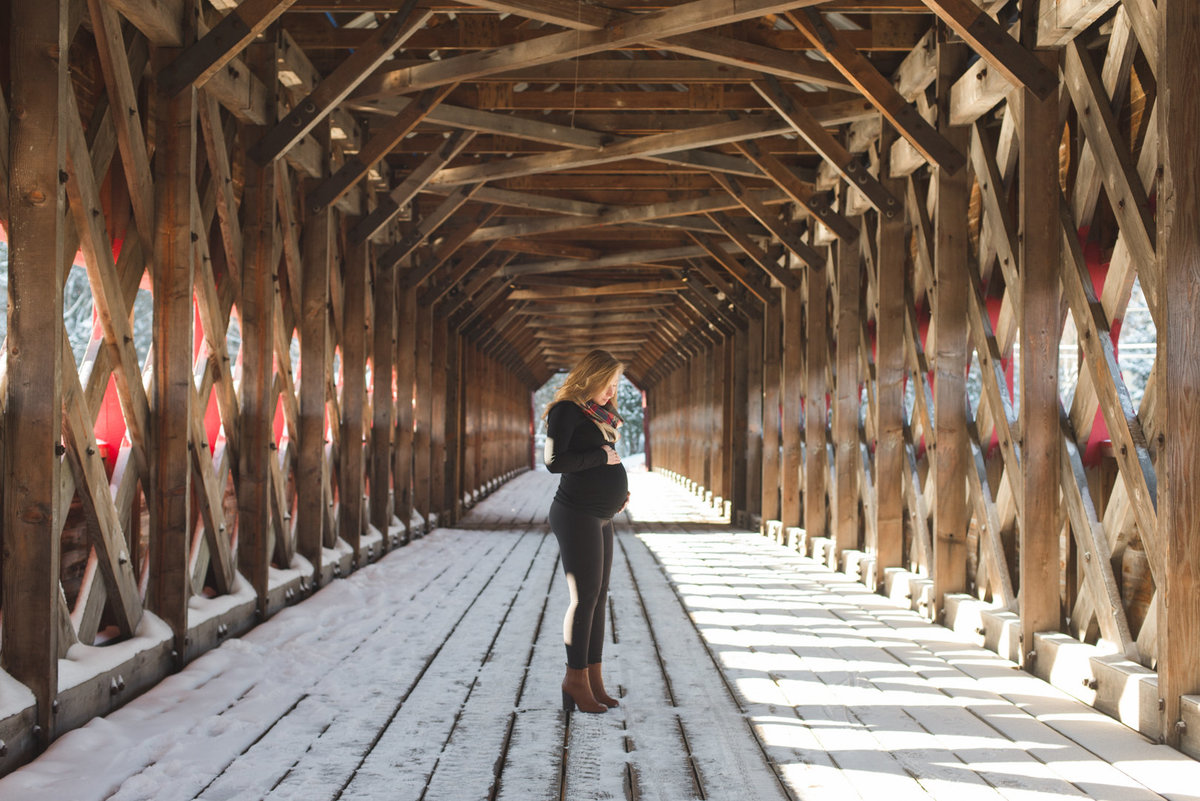 mom to be standing under covered wooden bridge in the winter