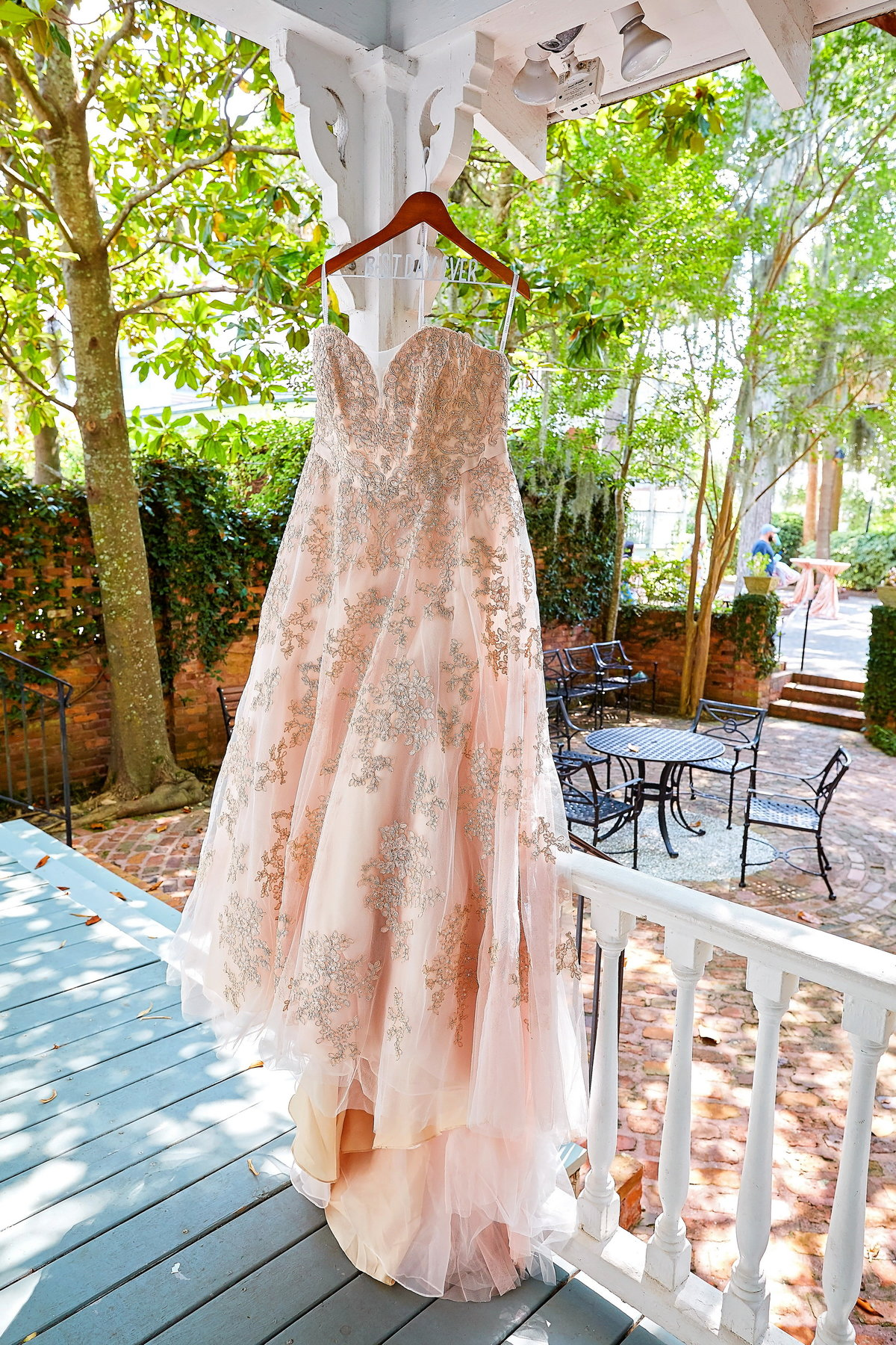 Blush, beaded wedding gown hanging on a porch at the Beaufort Inn, Beaufort, SC