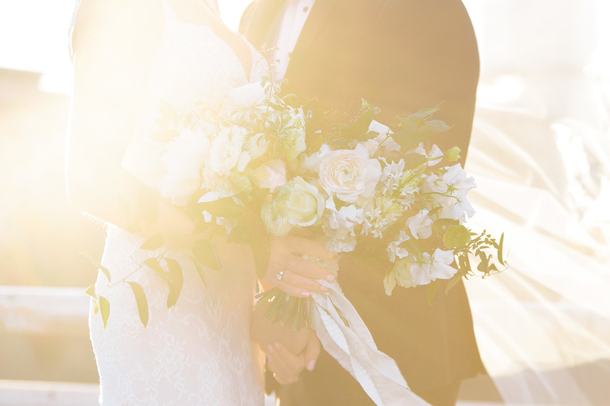 A bride and groom's embrace wrapped in golden sunlight.  Florals by Amy Osaba, photograph by Rebecca Cerasani.