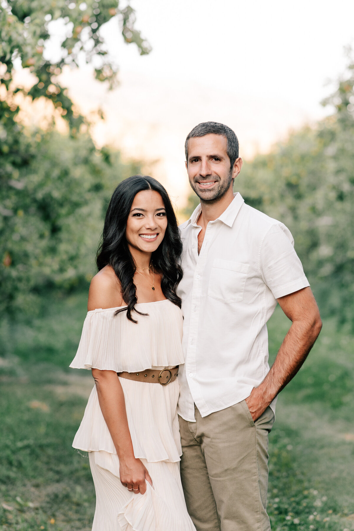 Portrait of couple in an orchard during engagement session at Beecher Hill House