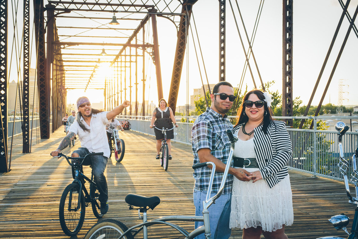 Engaged couple hanging out with their friend on Hays Street Bridge with their friends and bicycles.