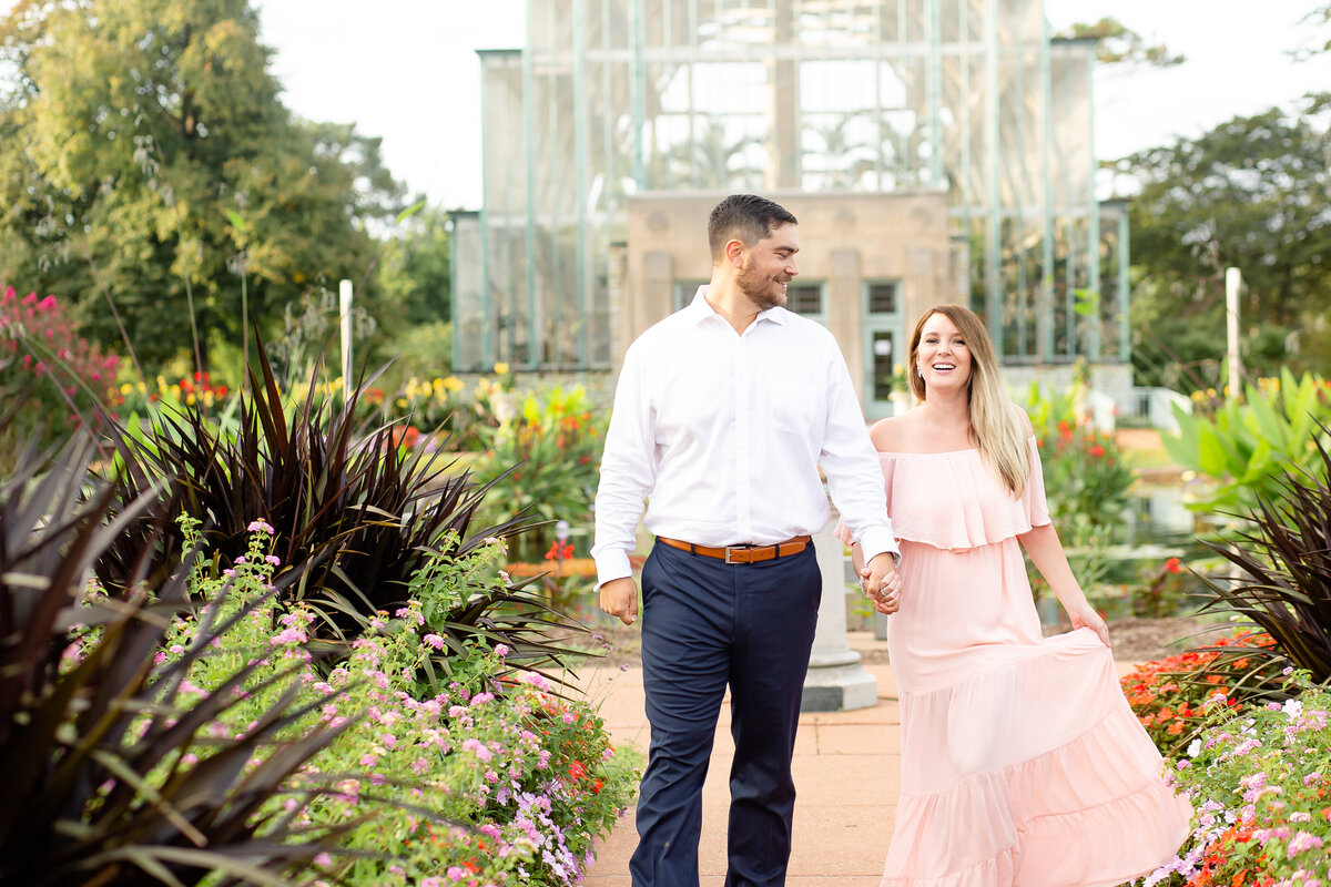 Summer Sunset Engagement Session with pink off the shoulder dress couple walking by flowers at the Jewel Box in Forest Park in St. Louis by Amy Britton Photography Photographer in St. Louis