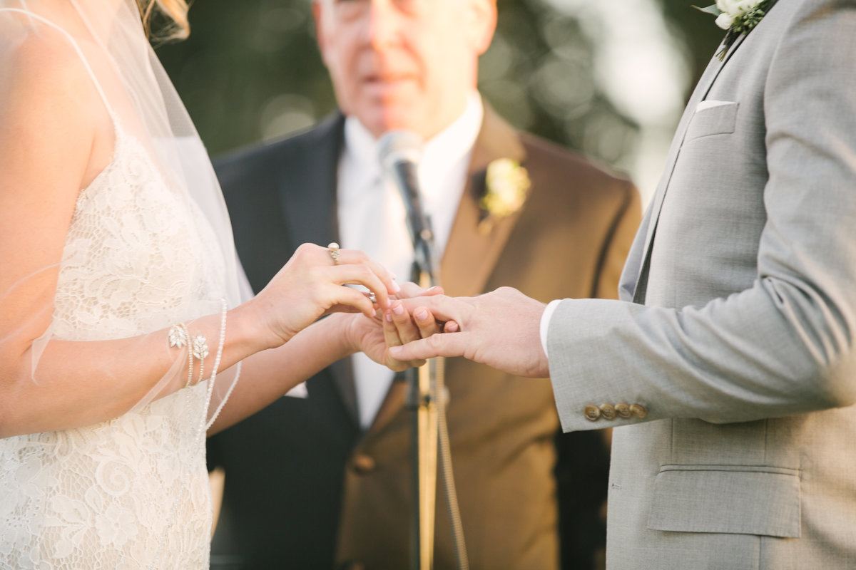 Bride puts on ring on grooms hand at Firestone Vineyard wedding