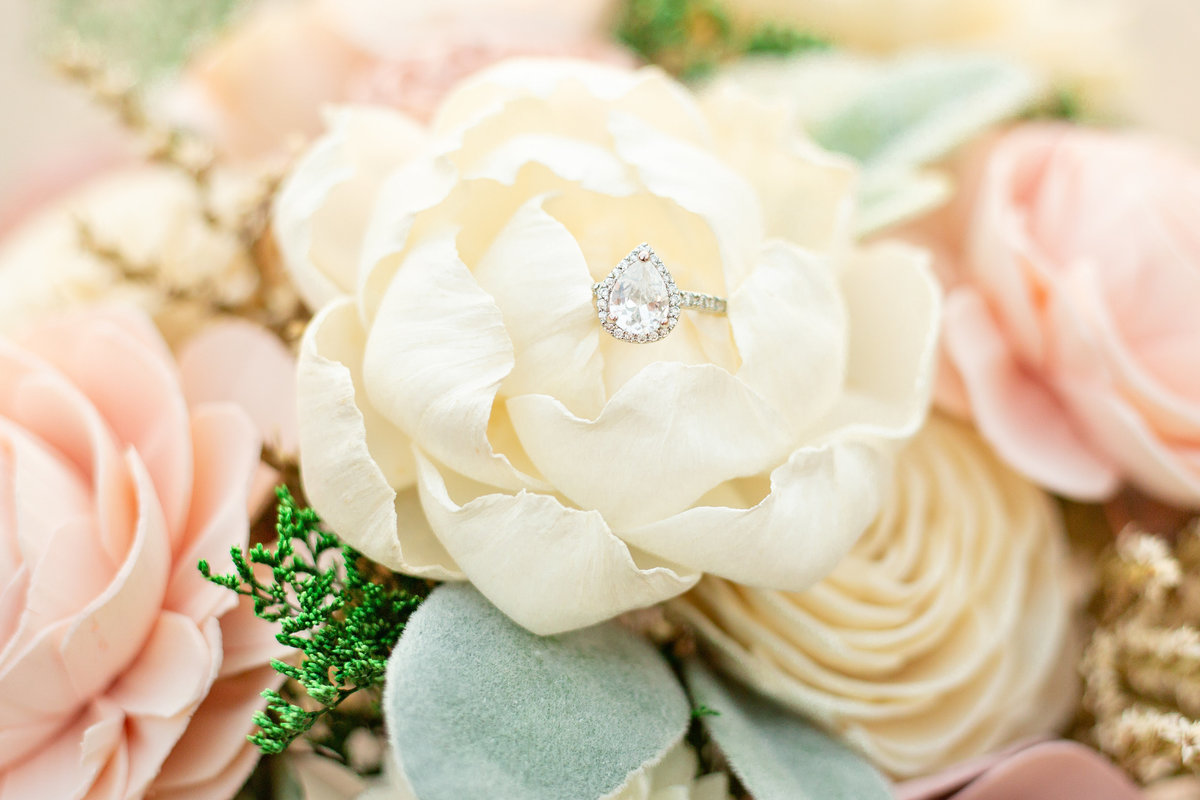 Close up of pear shaped engagement ring in cream, green and pink wedding bouquet