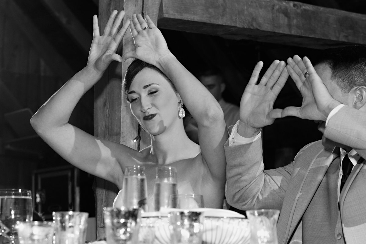 The bride and groom throw up the sign for JayZ at their Skinner Barn in Vermont fall wedding