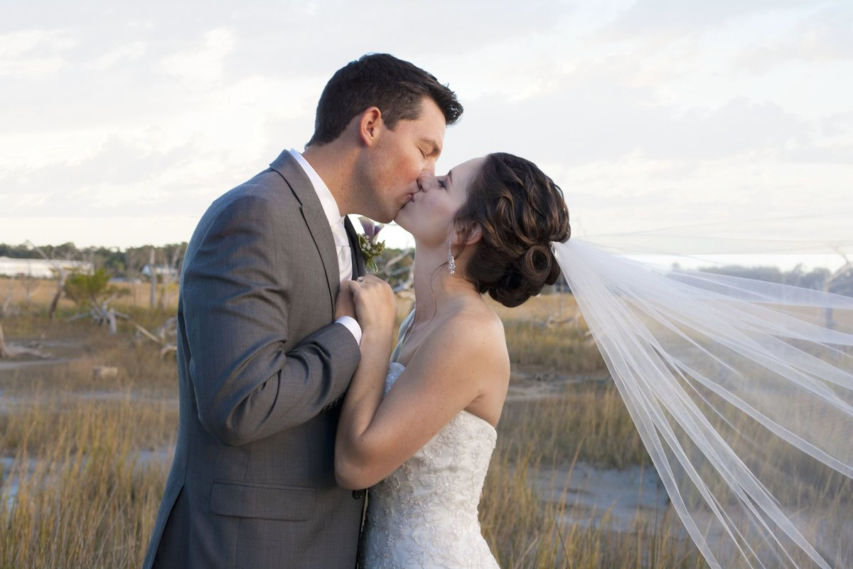 bride and groom kissing in front of marsh with veil blowing in the wind
