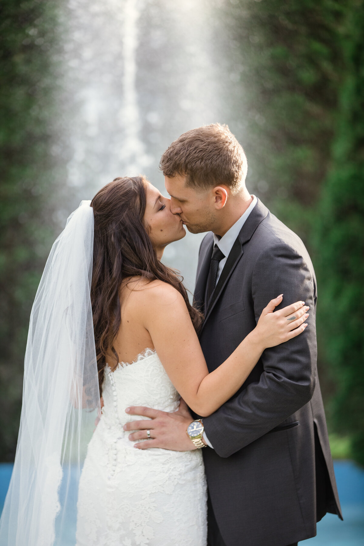 photo of bride and groom kissing near fountain at The Carltun
