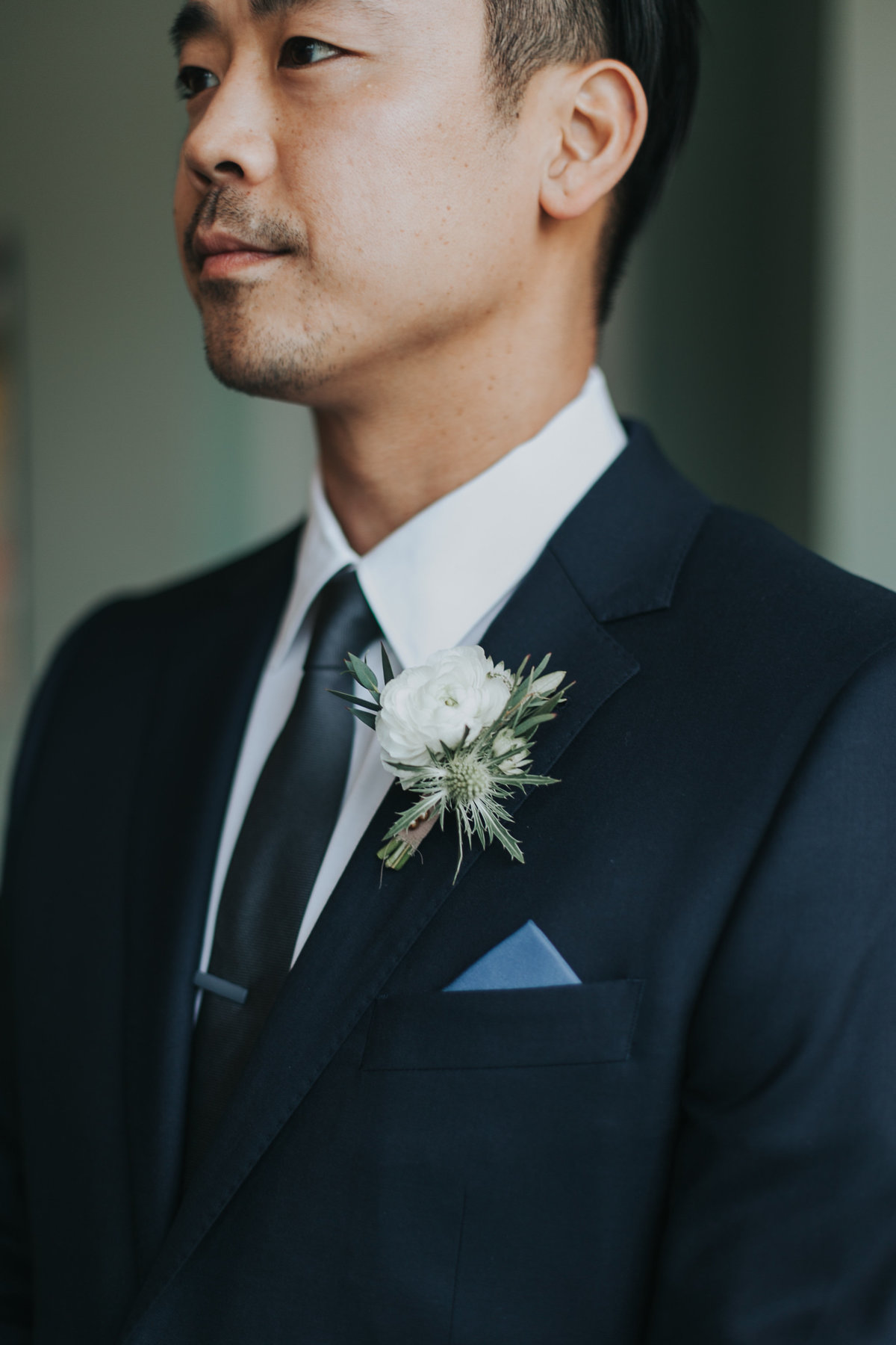 modern groom with black suit and blue pocket square at wedding at The Fig House