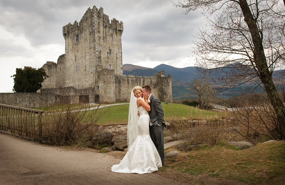 blonde bride wearing a mermaid style wedding dress and long veil being kissed by her husband wearing a dark grey tailcoat wedding suit while standing in front of Ross Castle, Killarney