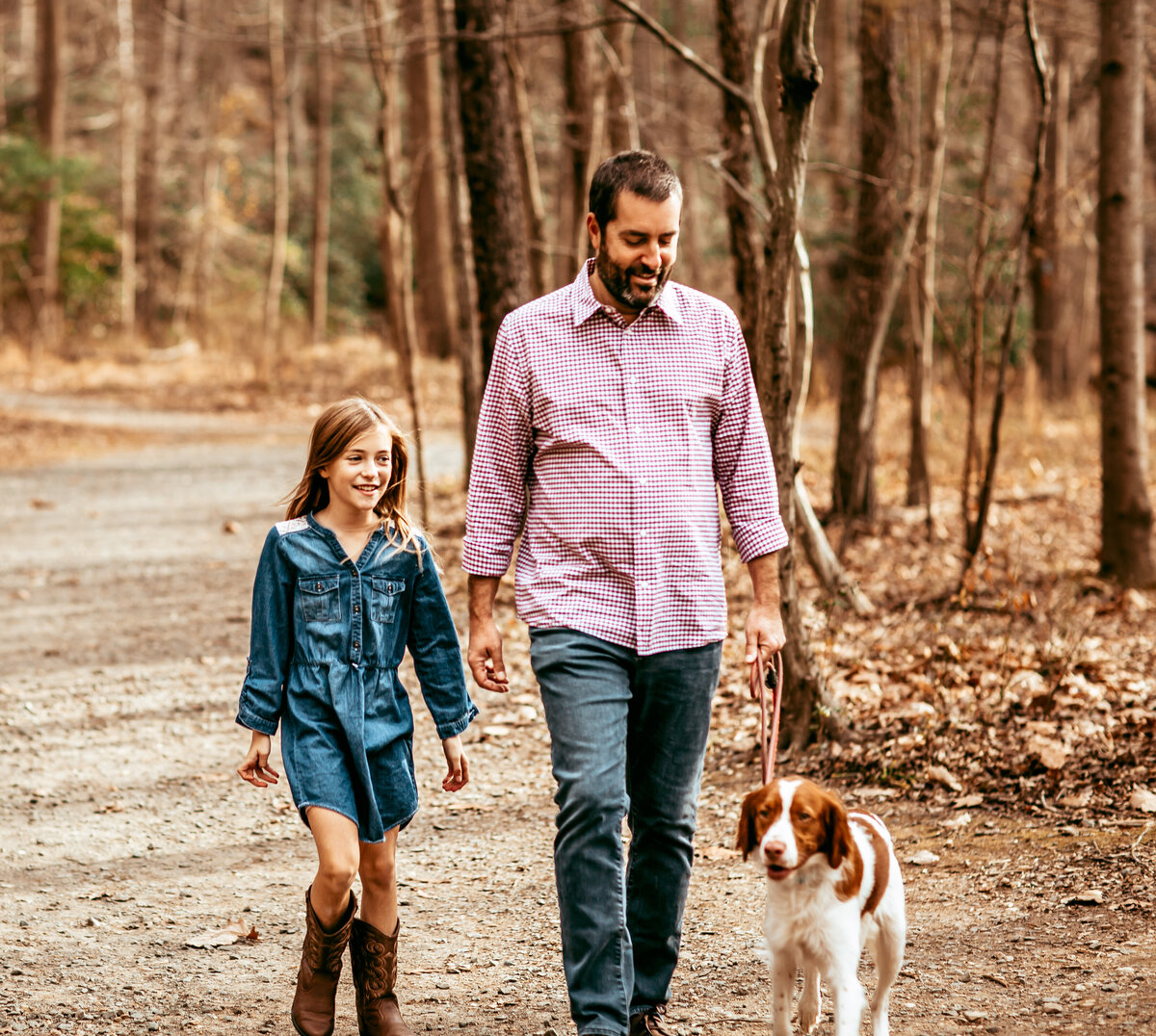 Father and Daughter walking in woods with dog