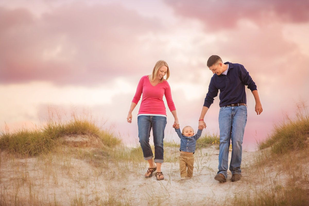 A sunset with pink colors during a family picture session in Laramie for a family with an adorable little boy.