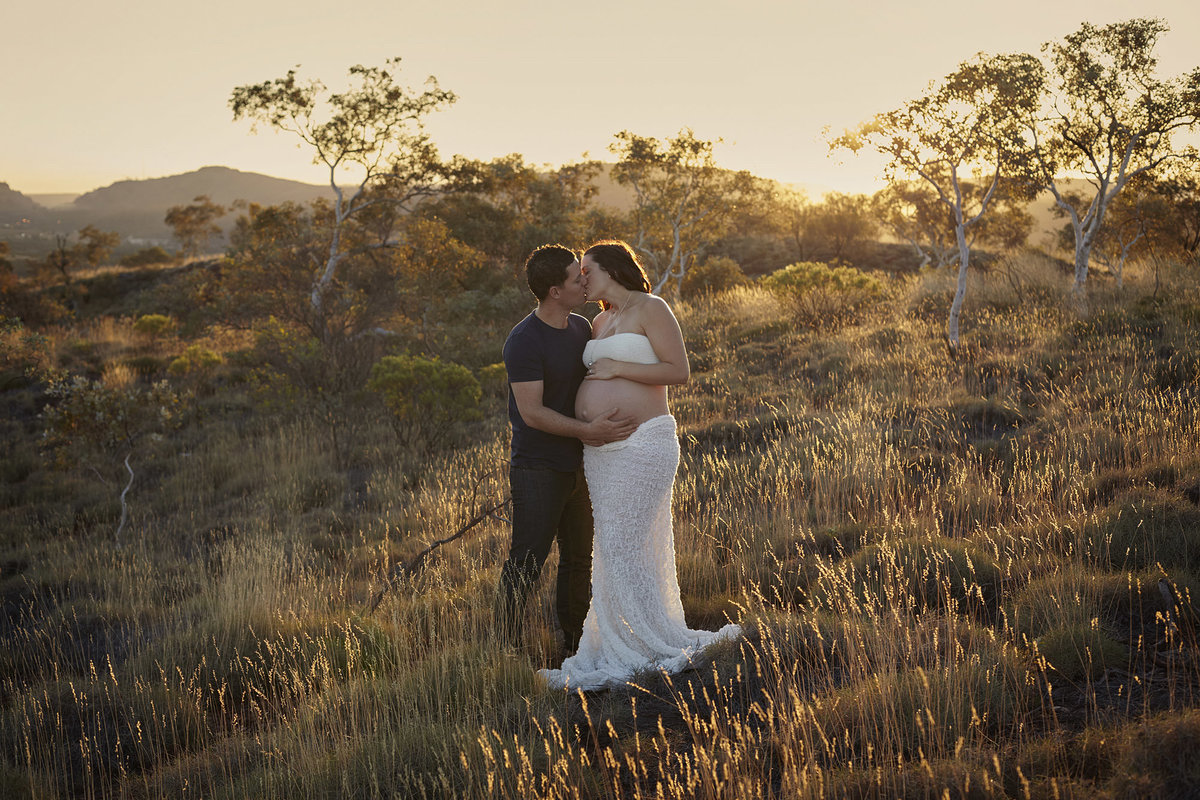 Pregnant wife and husband kissing and cuddling each other in natural bushland with golden sunlight