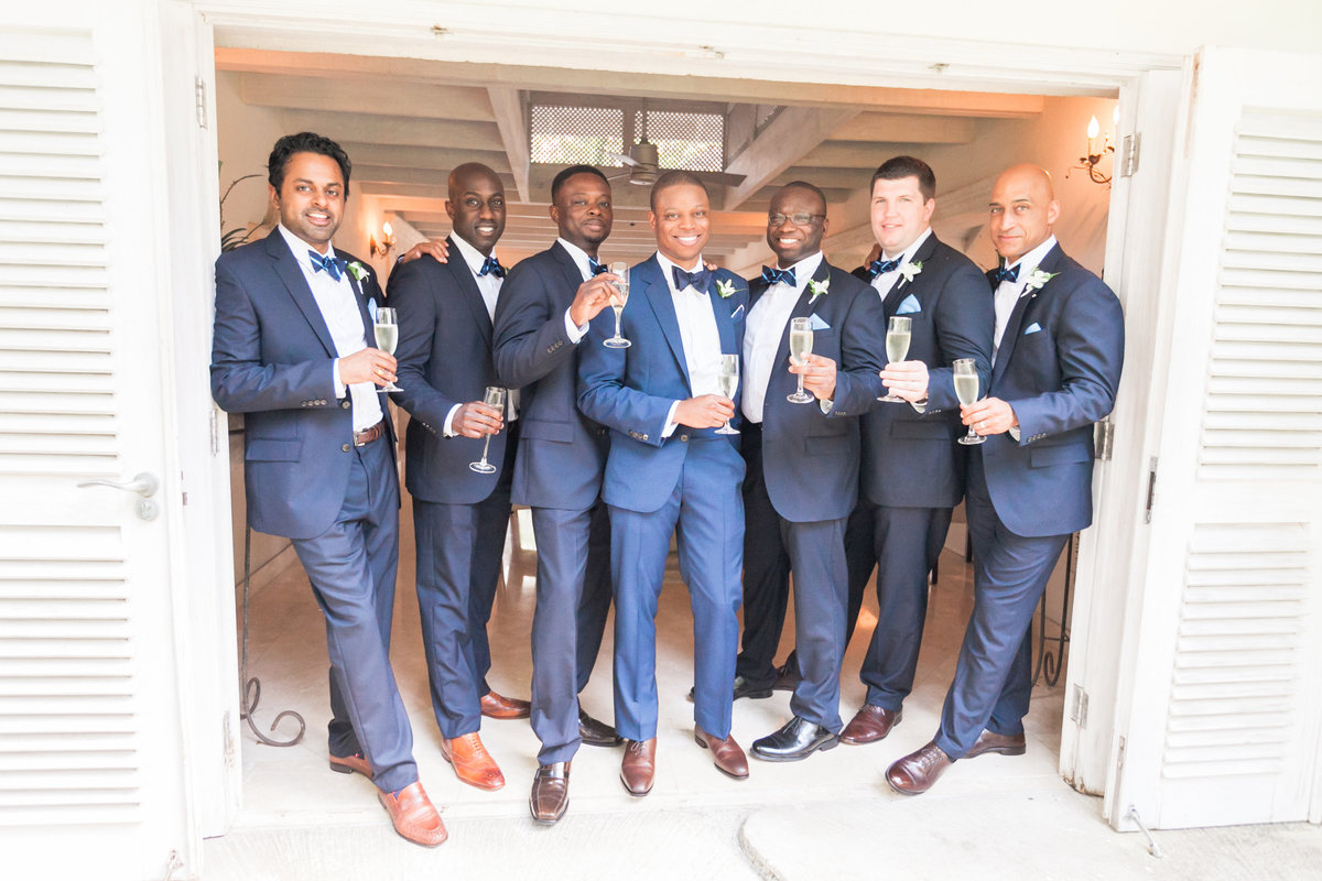 Groomsmen wearing navy suits from J. Crew and groom wearing custom suit from Brooklyn Tailors, bowtie by Thomas Pink | navy for black tie destination wedding in Barbados, Bluff House villa at Sandy Lane