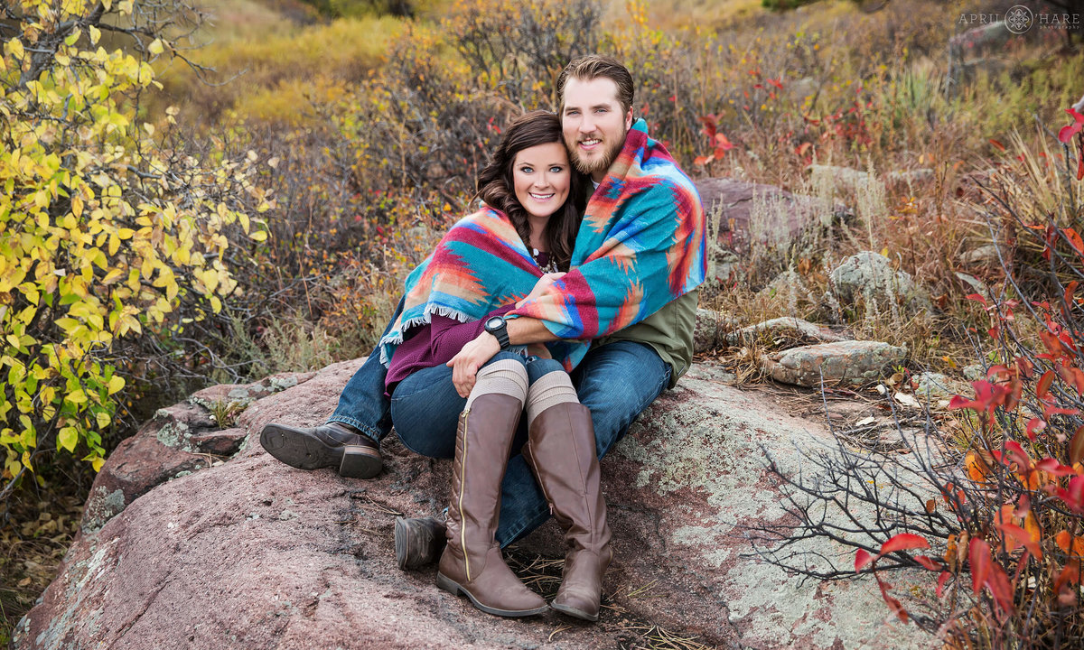 Snuggling up in printed blanket during Autumn at South Mesa trail Boulder Colorado Engagement Photography