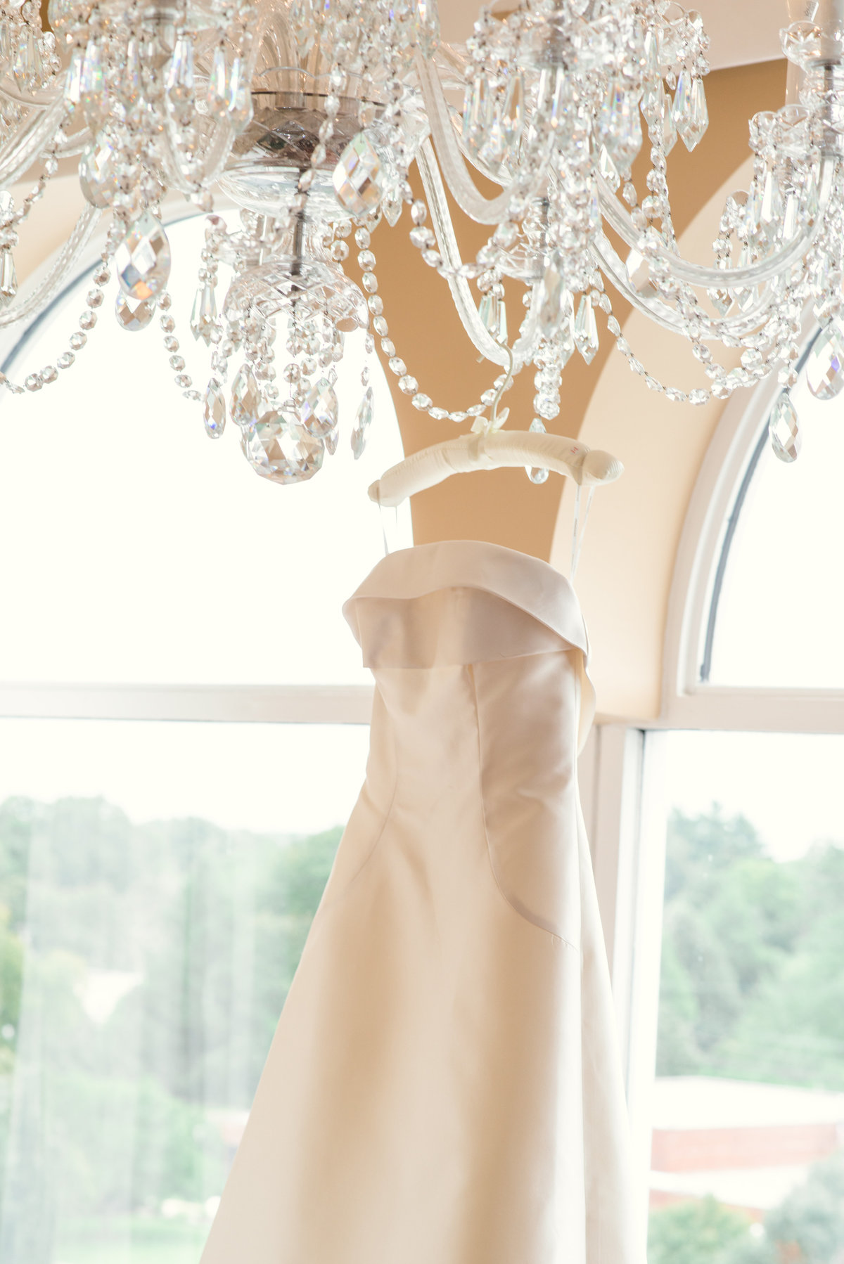 photo of bridal gown hanging on chandelier from inside The Garden City Hotel
