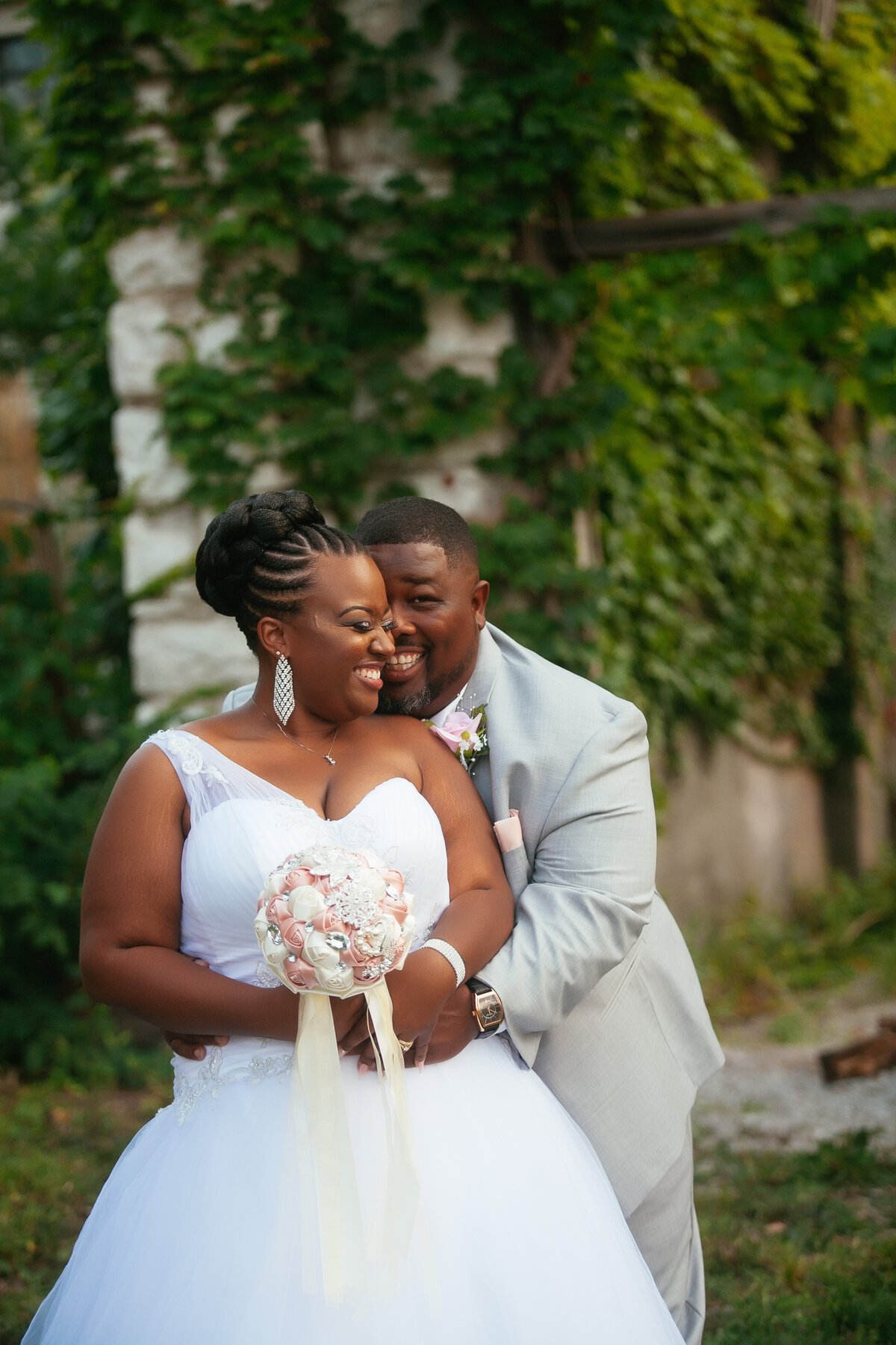 Black couple snuggles together at their summer wedding in St. Louis
