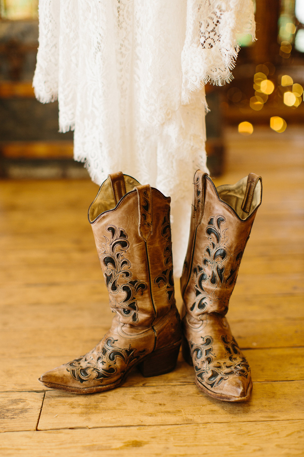 Cowboy boots on a wood floor next to a wedding dress.