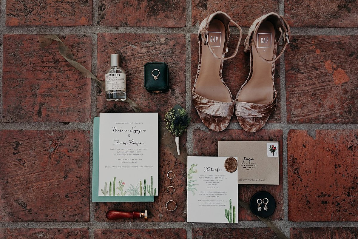 Bride's shoes, invitation, perfume, and rings displayed in wedding photo