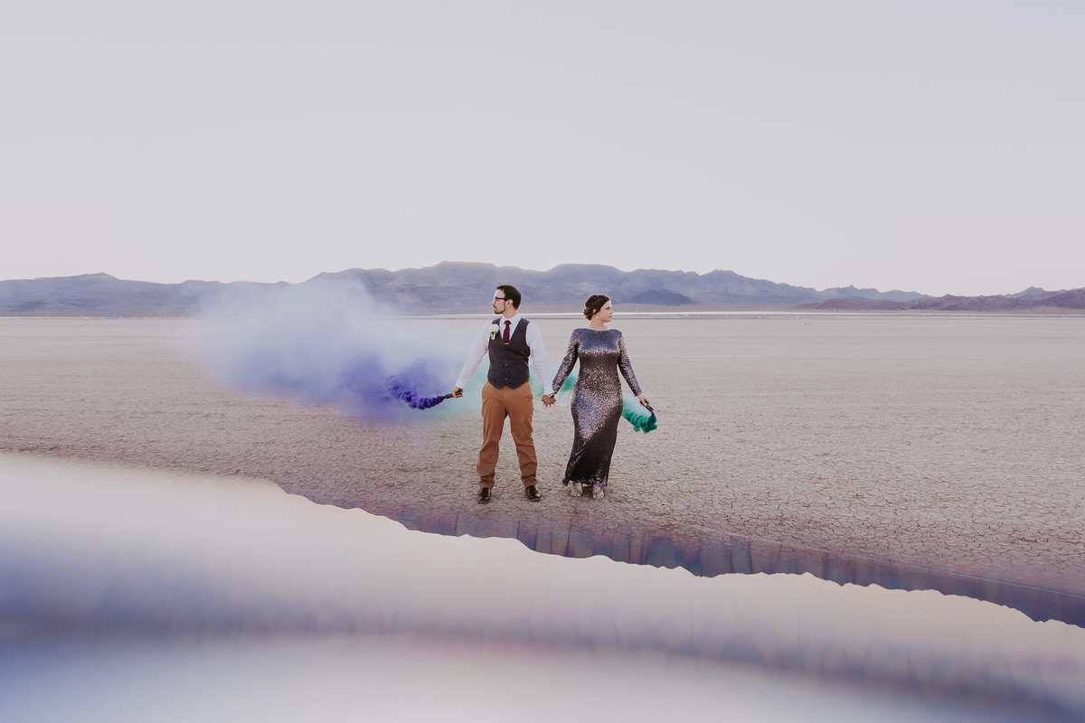 Lake tahoe elopement photographers couple holds colorful smoke and pose in desert