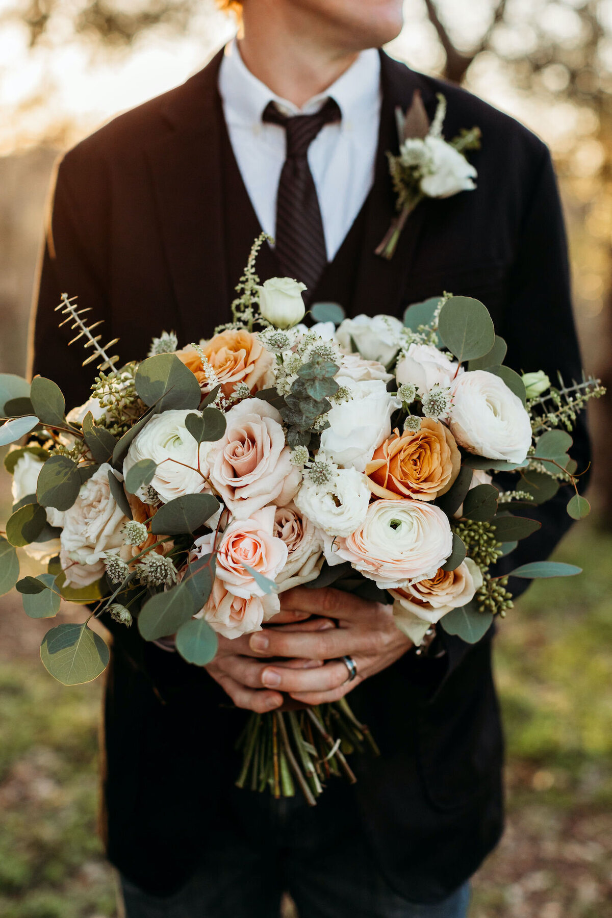 Groom holding white and orange wedding bouquet