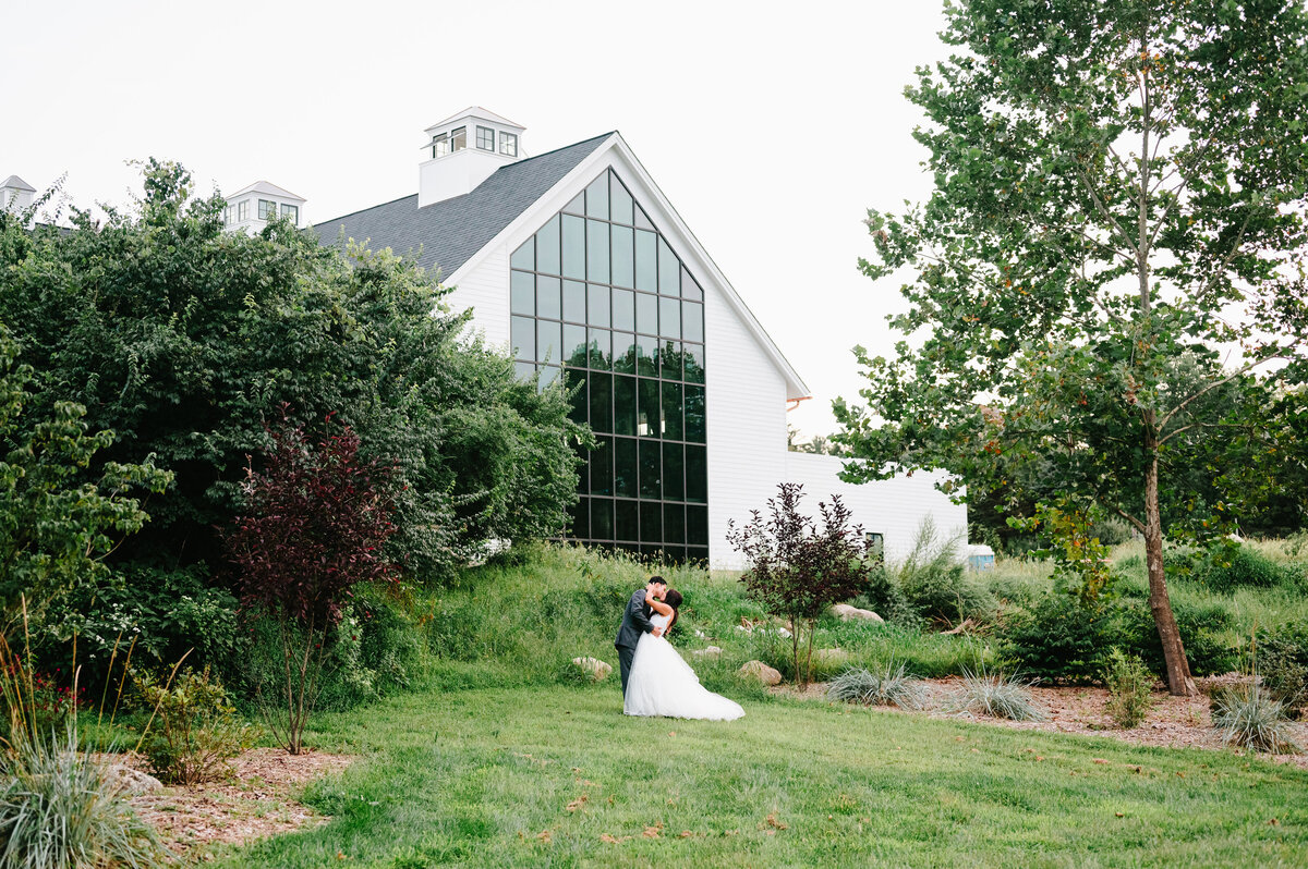 Bride and groom kiss and embrace on meadow in front of white farmhouse with floor to ceiling windows