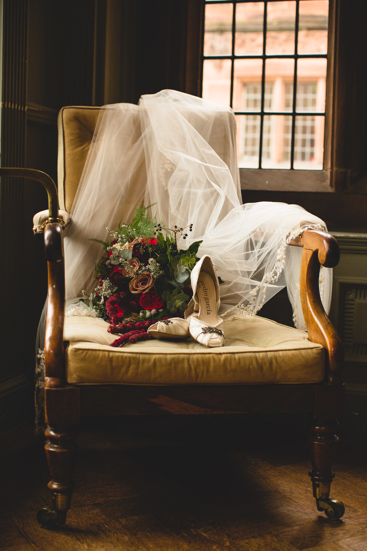 wedding shoes bouquet and veil on chair at thornton manor