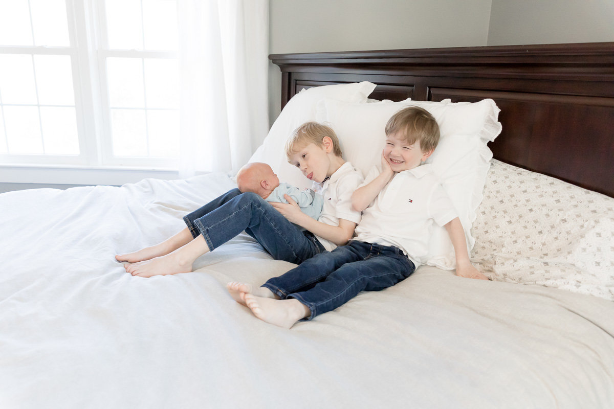 Big brothers being silly with newborn brother on mom and dad's master bed