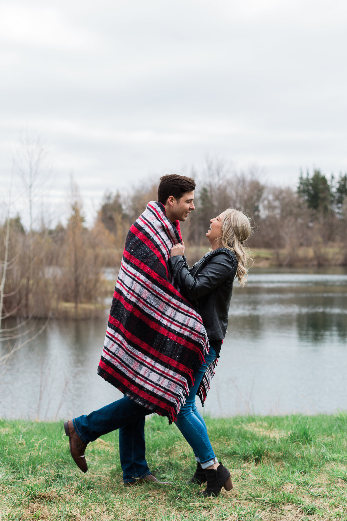 engagement photo of couple wrapped in blanket