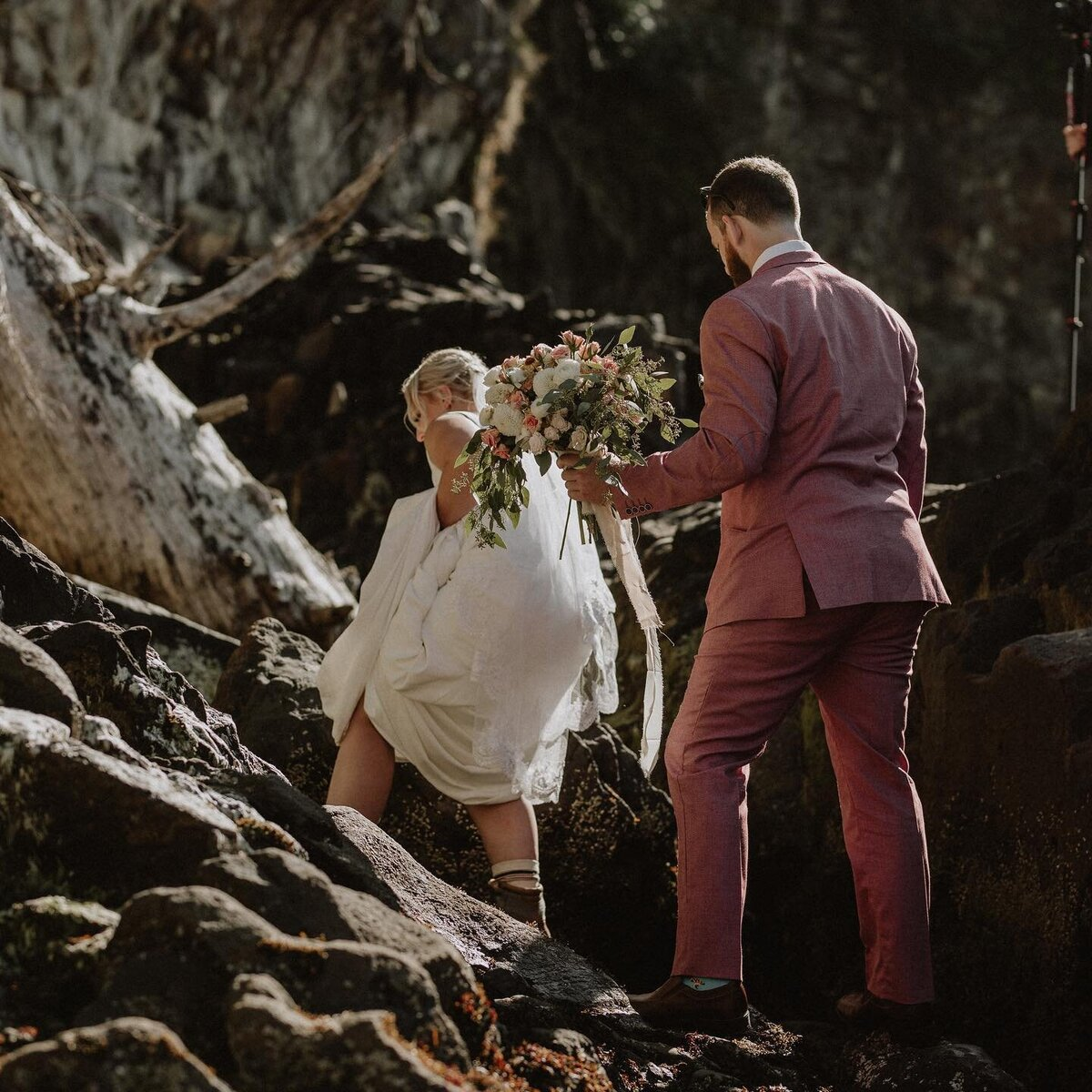 Couple hiking up cliff in wedding dress Oregon