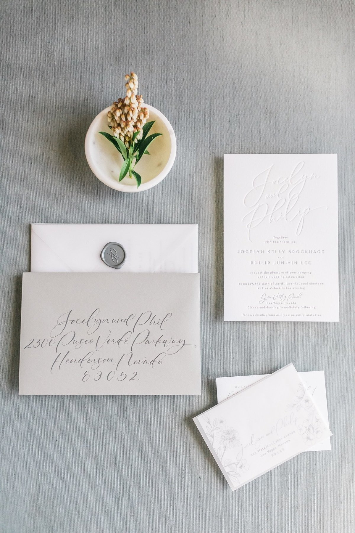 a picture of a wedding invitation suite with a wax seal, vellum sleeve, and blind letterpress at Green Valley Ranch Resort in Las Vegas