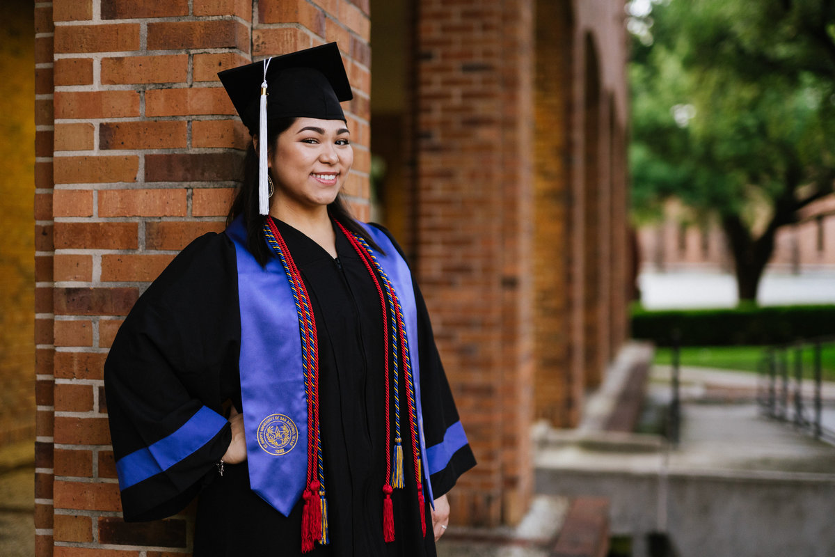 college senior leaning on a wall wearing cap gown