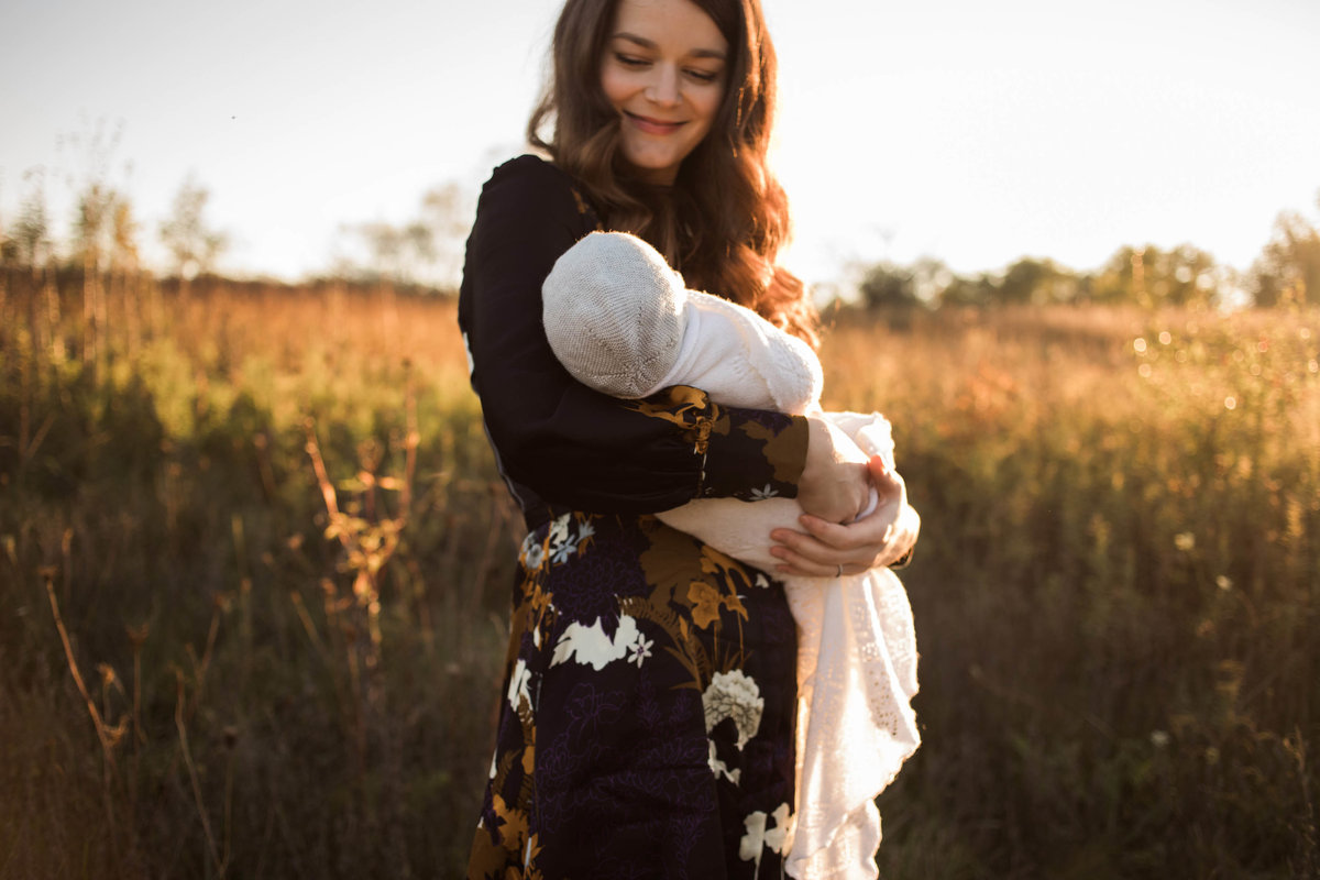 Laurie Baker captures a smiling mother with her beautiful newborn baby during sunset