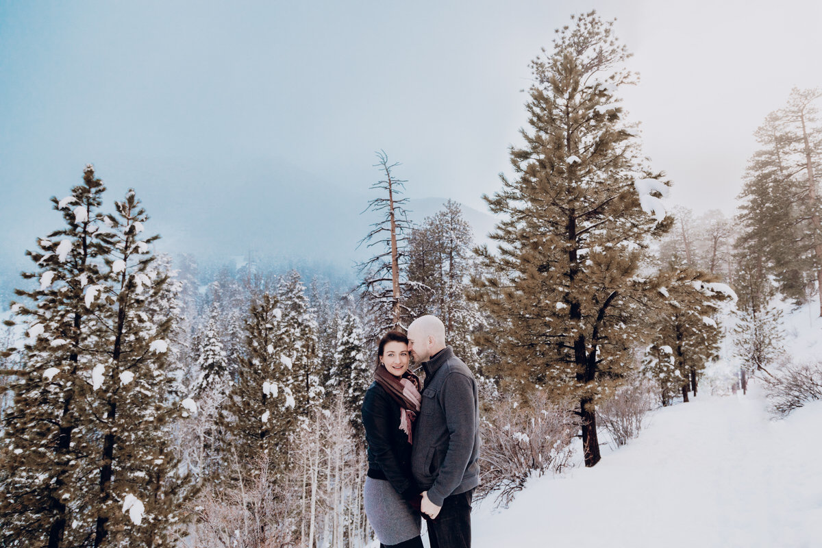 Lake tahoe engagement pictures couple kisses on snowy mountaintop